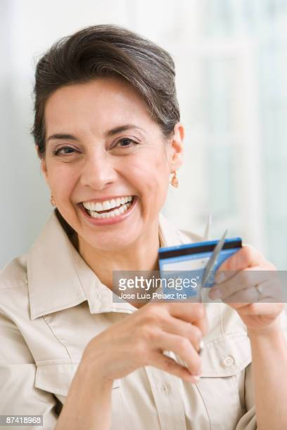 Hispanic woman cutting up credit card