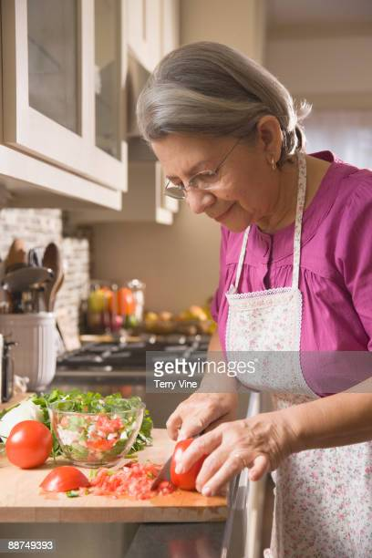 hispanic woman cutting vegetables - one senior woman only stock pictures, royalty-free photos & images
