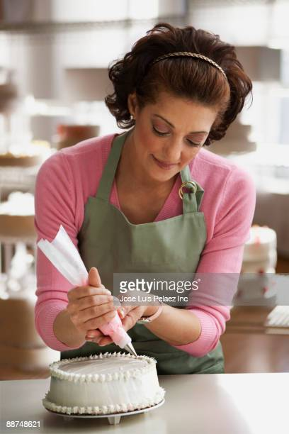hispanic woman decorating cake - decorating a cake stock pictures, royalty-free photos & images