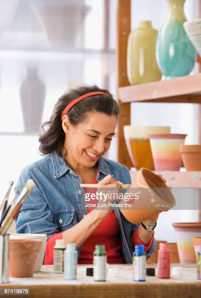 Hispanic woman decorating flower pot