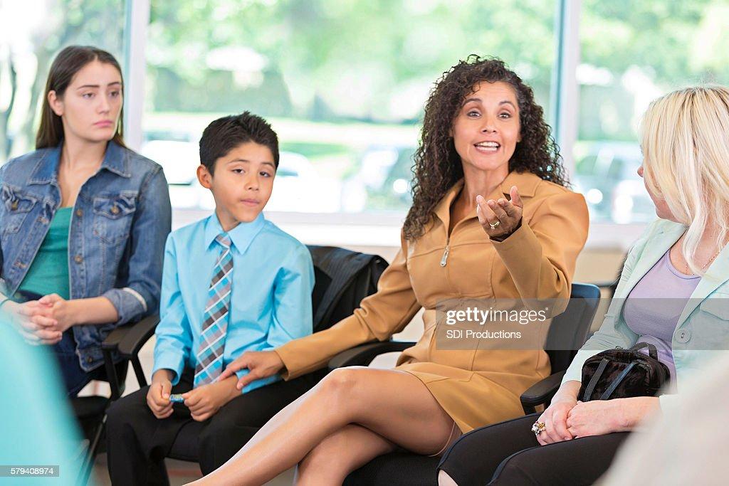 Hispanic woman defending her son in meeting : Stock Photo