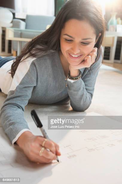 Hispanic woman drawing on floor
