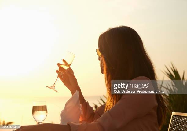 Hispanic woman drinking champagne at sunset dinner outdoors