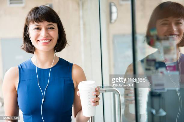 Hispanic woman drinking coffee and listening to earbuds