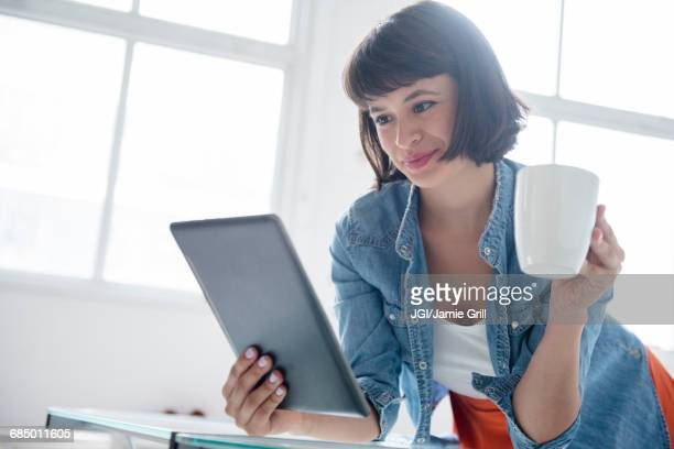 Hispanic woman drinking coffee and reading digital tablet