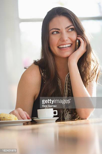 Hispanic woman drinking coffee and talking on cell phone
