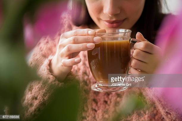 hispanic woman drinking coffee behind flowers - tea hot drink stock pictures, royalty-free photos & images