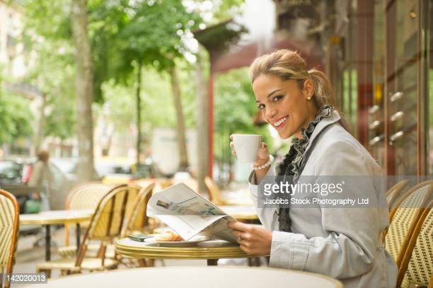 Hispanic woman drinking coffee in outdoor cafe