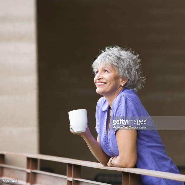 Hispanic woman drinking coffee on balcony