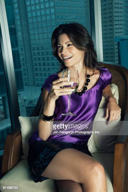 hispanic woman drinking white wine - evening wear stock pictures, royalty-free photos & images