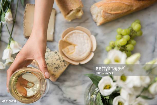 hispanic woman drinking wine with cheese - white wine stock pictures, royalty-free photos & images