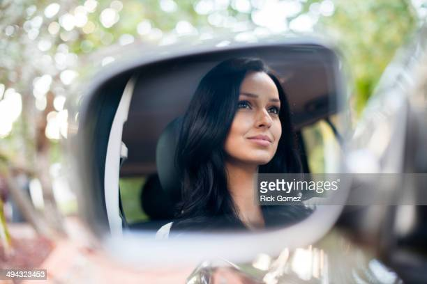 hispanic woman driving car - side view mirror stock photos and pictures