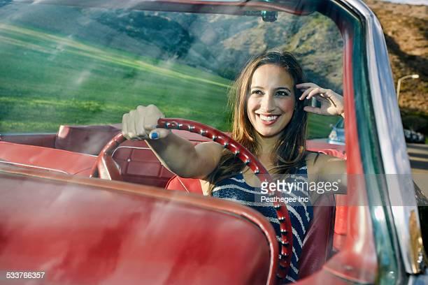 Hispanic woman driving in classic convertible