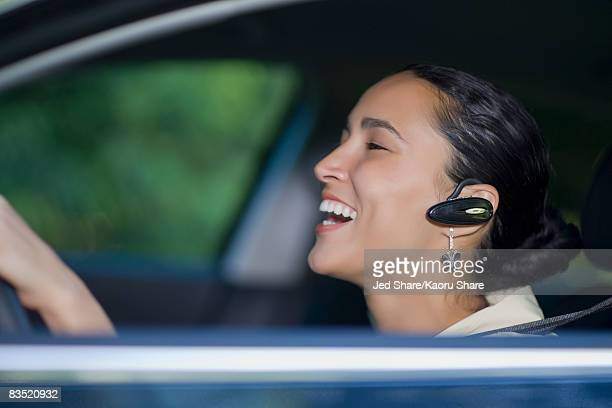 Hispanic woman driving with hands-free cell phone device