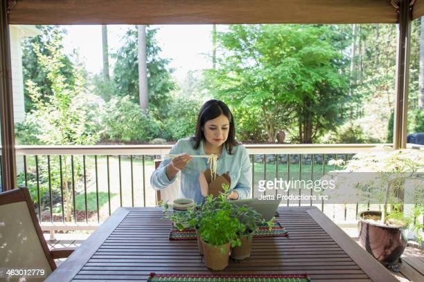 Hispanic woman eating Chinese food on patio