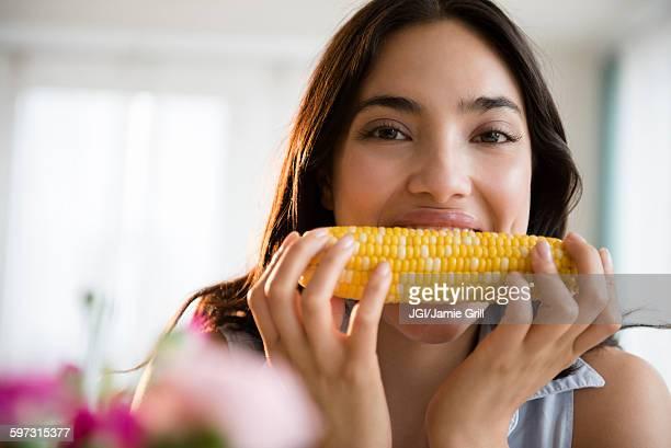 Hispanic woman eating corn on the cob