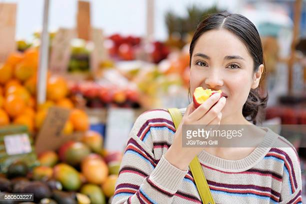 Hispanic woman eating fruit at farmers market