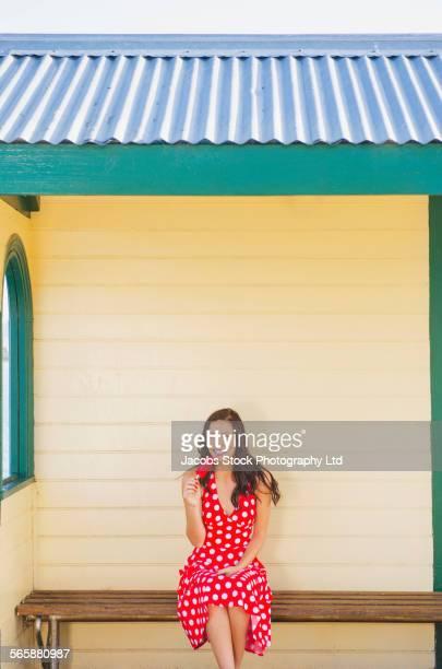 Hispanic woman eating popsicle on bench