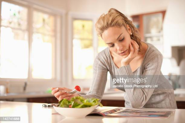 Hispanic woman eating salad and reading magazine