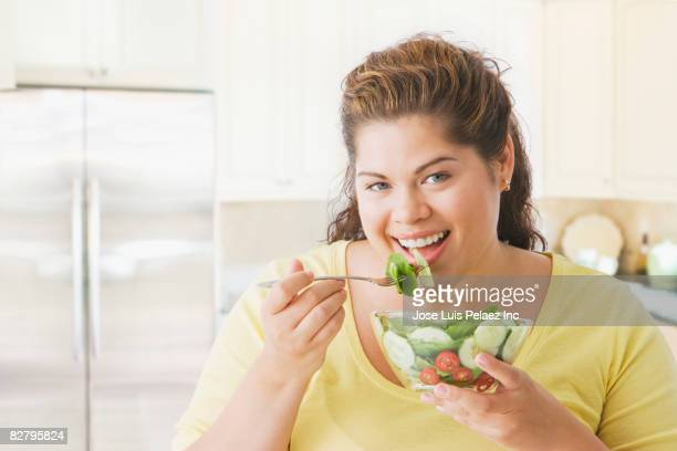 hispanic woman eating salad - fat nutrient stock pictures, royalty-free photos & images