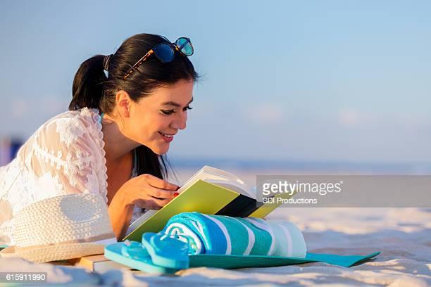 Hispanic woman enjoys reading book on the beach