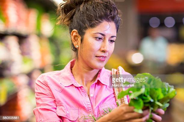 Hispanic woman examining produce at grocery store