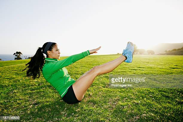 hispanic woman exercising in field - sit ups stock photos and pictures