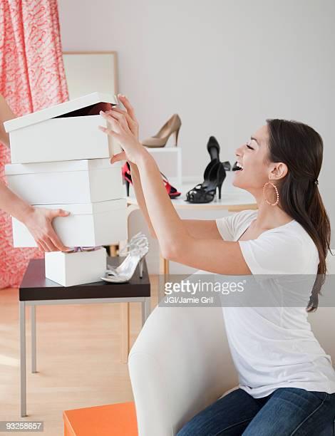 Hispanic woman eyeing shoe boxes at store