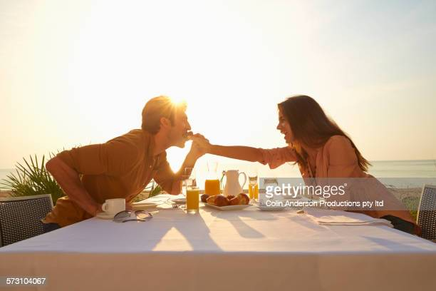 Hispanic woman feeding man at sunset dinner outdoors