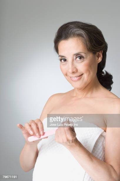 Hispanic woman filing fingernails