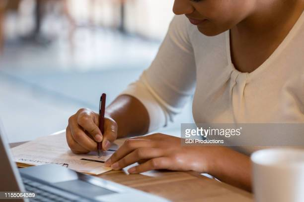 hispanic woman fills out job application at coffee shop - form filling stock pictures, royalty-free photos & images
