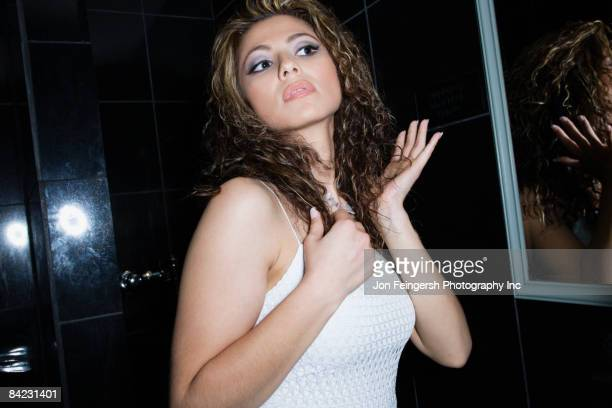 hispanic woman fixing her hair in nightclub restroom - arrogance stock pictures, royalty-free photos & images