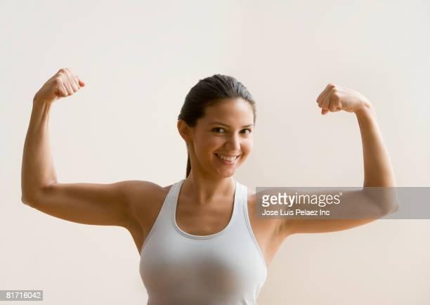 Hispanic woman flexing biceps muscles