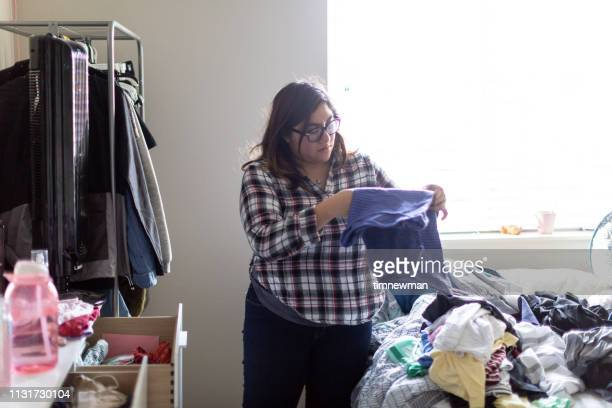 hispanic woman folding laundry at home - trousers stock pictures, royalty-free photos & images