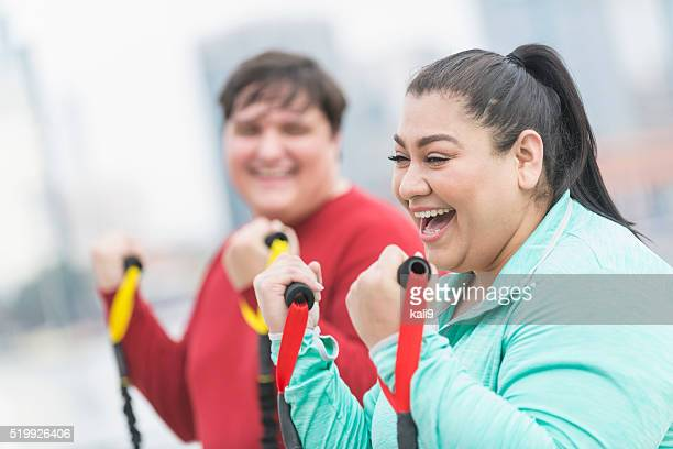 hispanic woman, friend exercising with resistance bands - chubby men stock photos and pictures