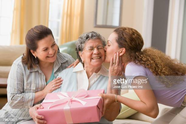 hispanic woman giving gift to grandmother - mais de 80 anos imagens e fotografias de stock