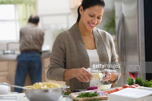 Hispanic woman grating cheese