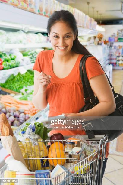 Hispanic woman grocery shopping with list