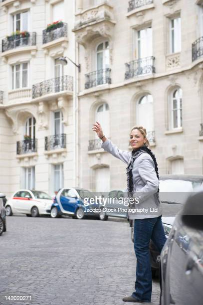 Hispanic woman hailing a taxi in city