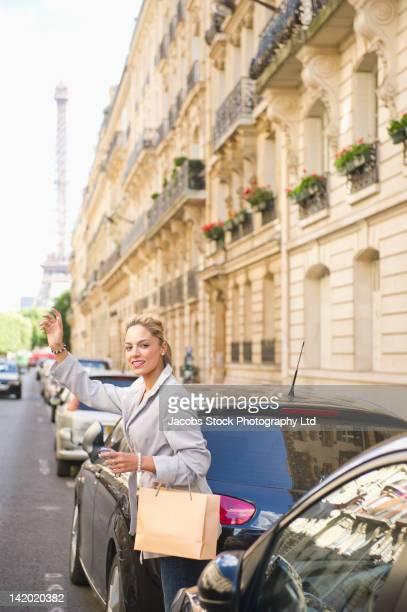 Hispanic woman hailing a taxi on city street