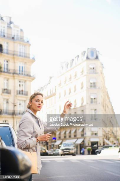 Hispanic woman hailing a taxi on city street