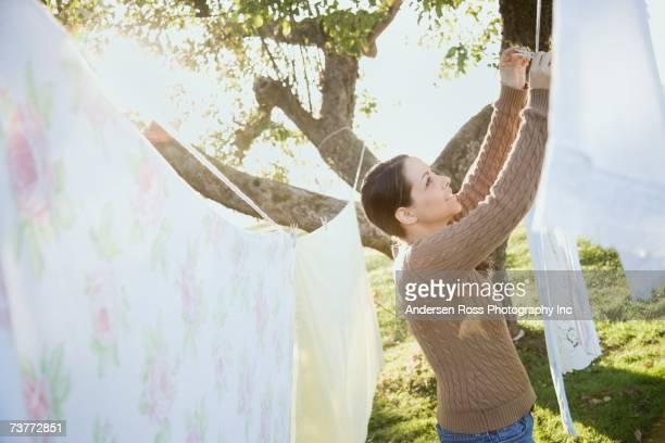 Hispanic woman hanging laundry on clothesline