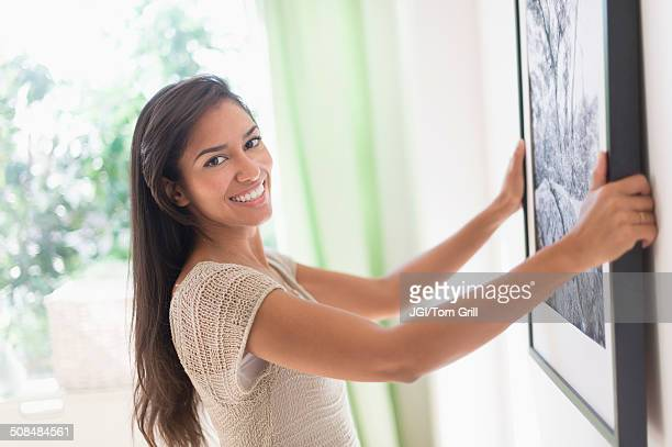 Hispanic woman hanging picture in living room