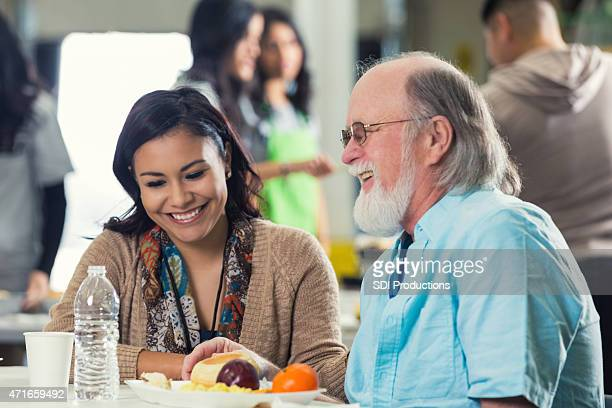 hispanic woman having meal with senior man in food bank - depression bread line stock pictures, royalty-free photos & images