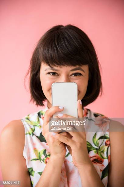 Hispanic woman hiding face behind cell phone