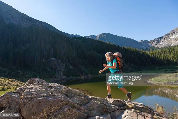 Hispanic woman hiking on boulder