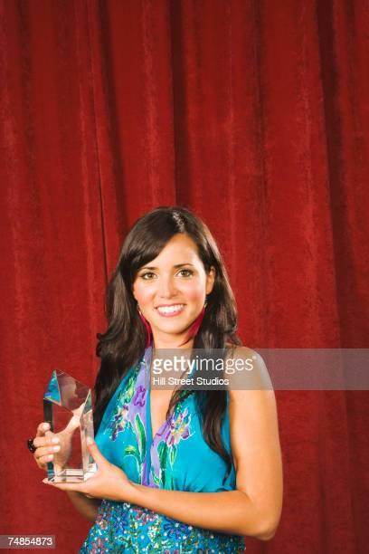 Hispanic woman holding award