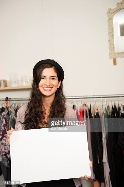 Hispanic woman holding blank card in shop