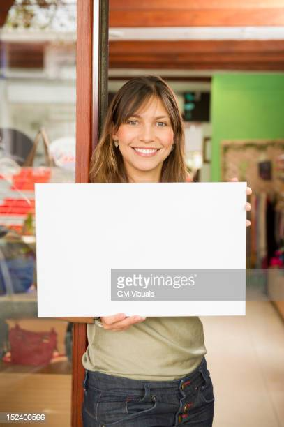 hispanic woman holding blank sign in store - person holding blank sign stock pictures, royalty-free photos & images