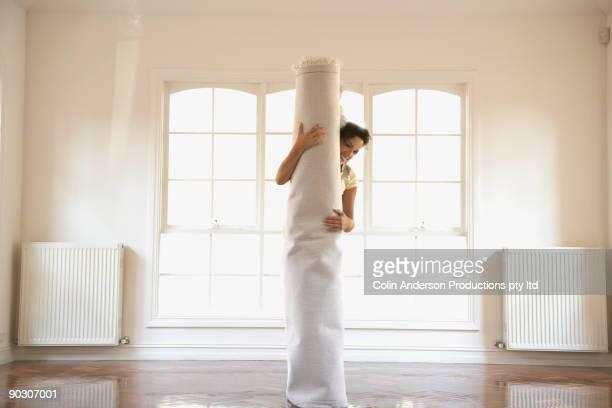 Hispanic woman holding carpet in new home